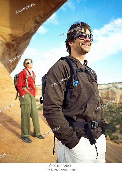 Two men hiking on red rocks