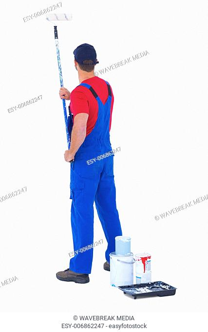 Rear view of handyman painting with roller on white background