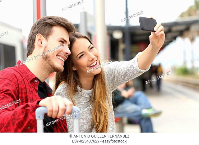 Couple of travelers photographing a selfie with a smartphone in a train station