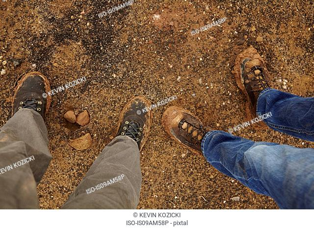 Overhead view of legs standing on gravel road