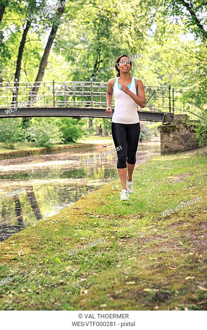 Geramny, Bavaria, Bayreuth, Woman jogging by a river in the city park