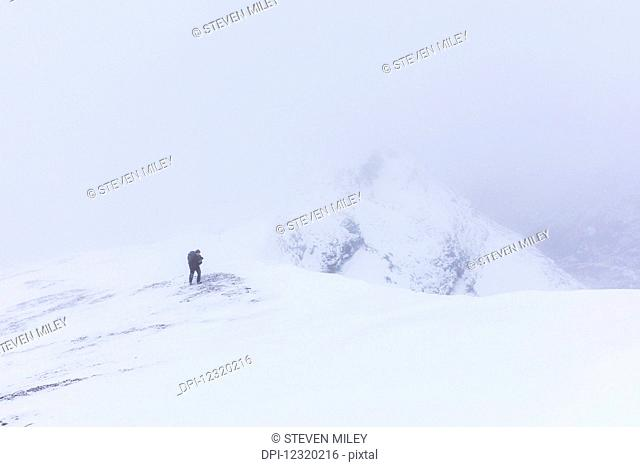 A hiker climbs a ridge high above Trims Creek in a portion of the Alaska Range known as the 'Delta Mountains' in early winter; Alaska, United States of America