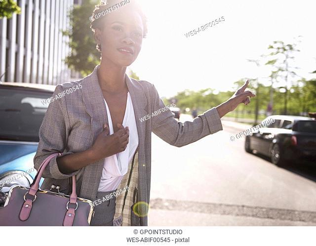 Portrait of businesswoman hailing a taxi