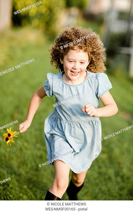 Happy little girl running on a meadow in the garden