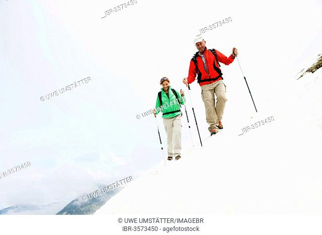 Couple moving over a snow field during their hike to Mt. Neunerkoepfle