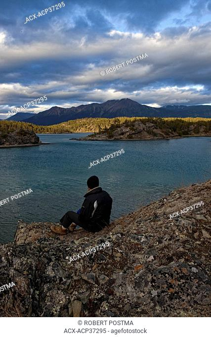 Man sitting on rocks watching the sunset light hitting an island on Atlin Lake in Atlin Provincial Park, Atlin, British Columbia, Canada