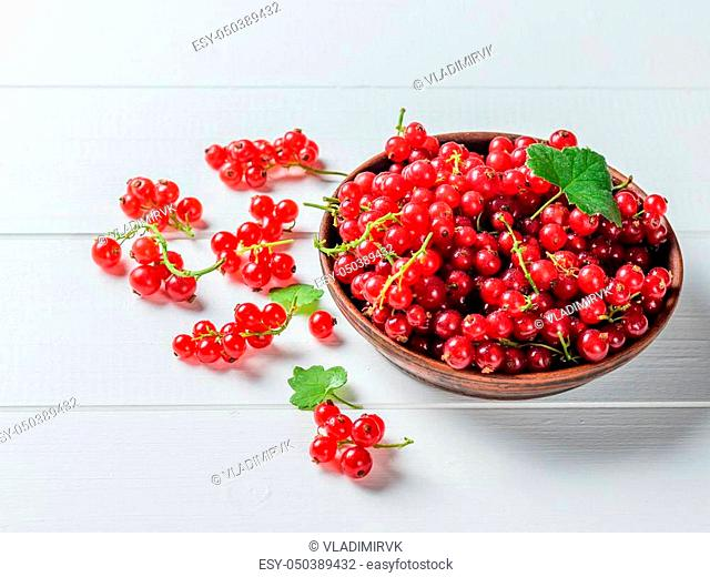Freshly picked redcurrant berries in a clay bowl on a rustic table. The concept of healthy natural food