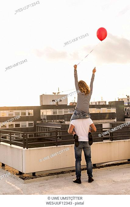 Back view of young couple on roof terrace at sunset