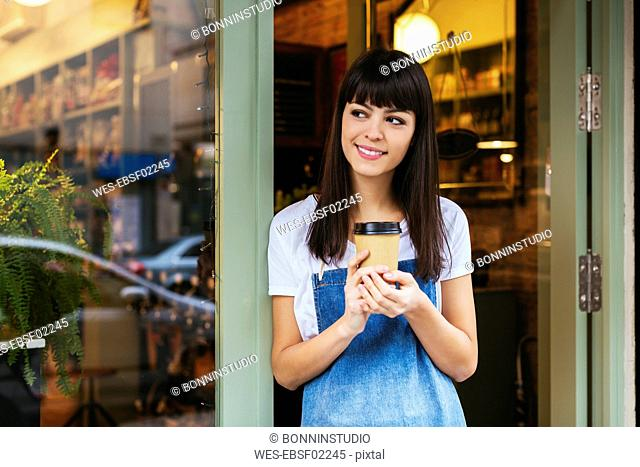 Smiling woman standing at entrance door of a store holding takeaway coffee