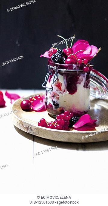 Semolina pudding with jam, berries and rose petals in a flip-top jar