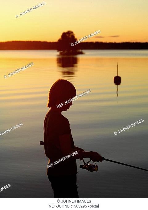Boy fishing on sea at dusk