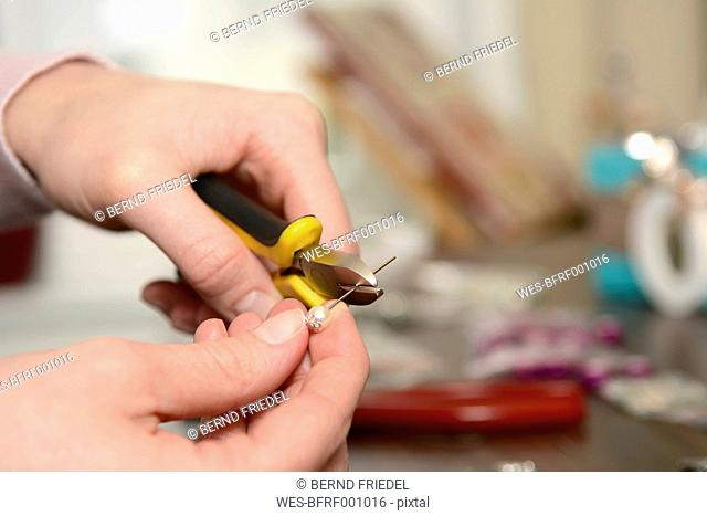 Young woman working on self-made earring