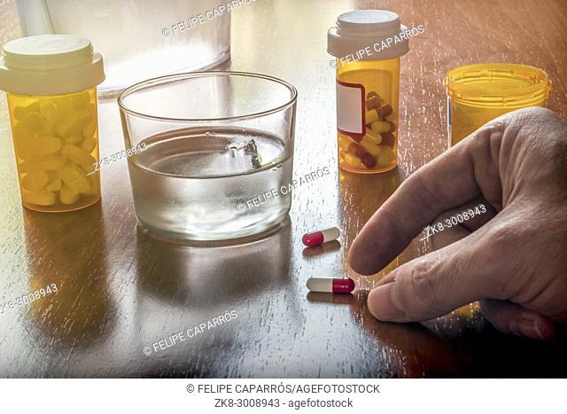 Old person taken its daily medication with a water glass