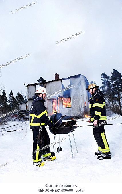 Firefighters having barbeque in front of burning house