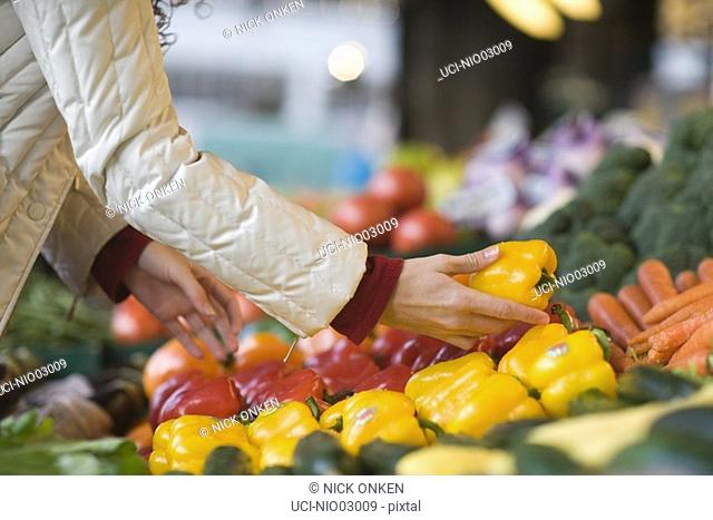 Young woman choosing bell peppers