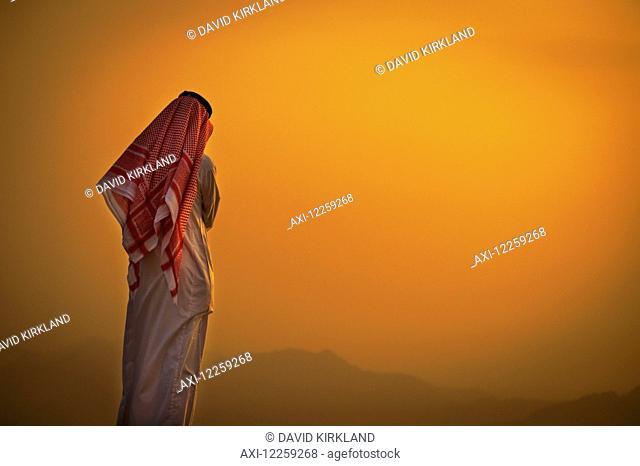 Saudi standing to watch the glowing orange sunset; Taif, Saudi Arabia
