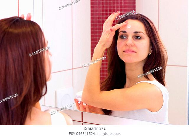 Young pleasant woman with long dark hair in white shirt using face cream in front of the mirror in her bathroom
