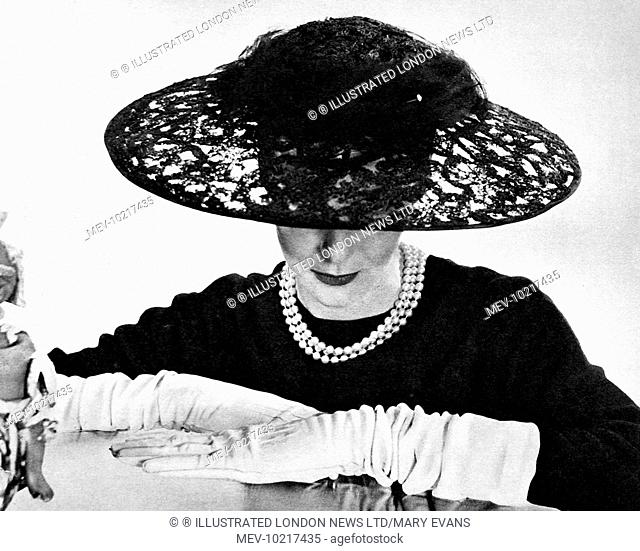Illustration showin a black lace straw Ascot hat, it's large crown swathed with net, 1955