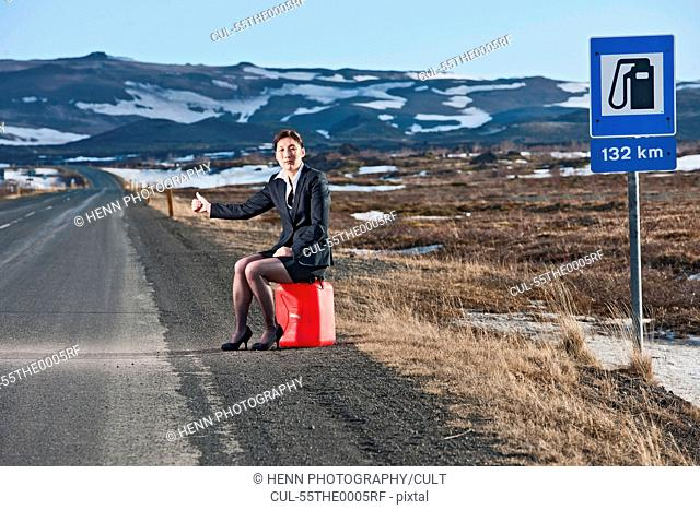Woman sitting on petrol can at roadside hitchhiking