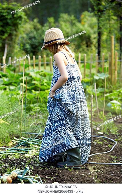 Girl in blue dress walking through field