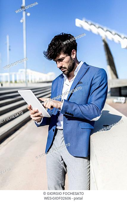 Young businessman using tablet outdoors