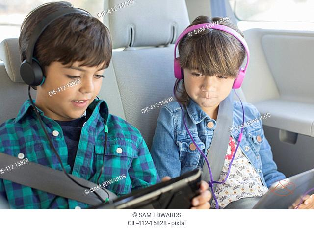 Brother and sister with headphones using digital tablets in back seat of car