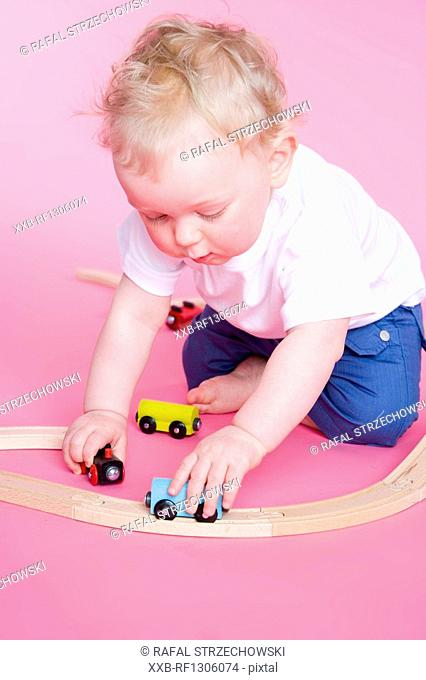 small boy playing with cars