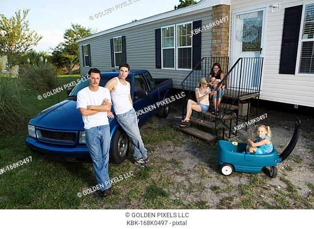 Blue-collar families in front of a trailer home
