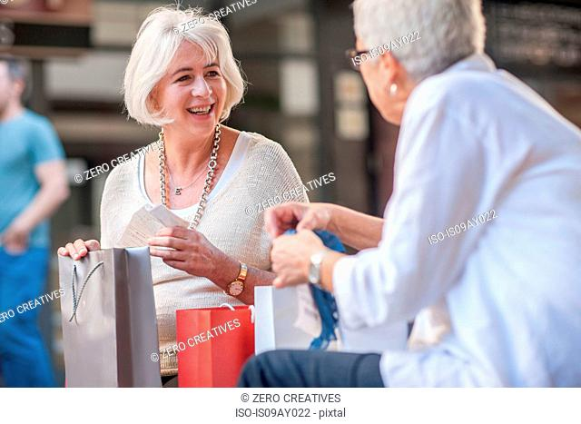 Mature women looking in shopping bags at shopping mall