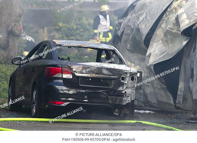06 May 2019, Schleswig-Holstein, Kiel: A car damaged by flames is parked in a parking lot. A warehouse of a forwarding company had caught fire at the...