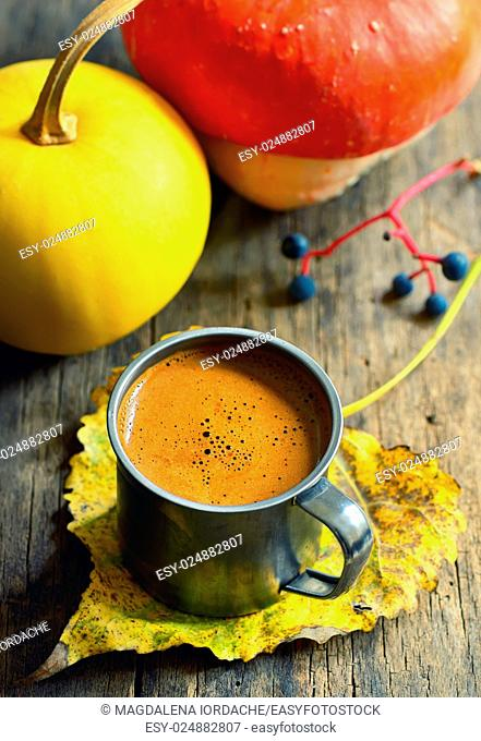 Cup of coffee on autumn leaf on the wooden background
