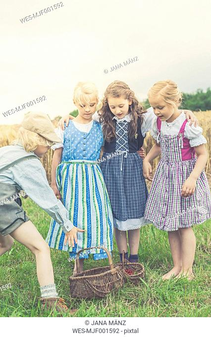 Germany, Saxony, three little girls looking while a boy reaching for basket with fruits