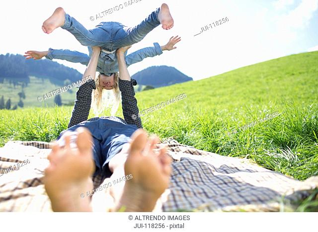 Father Balancing Daughter On Arms In Countryside Field