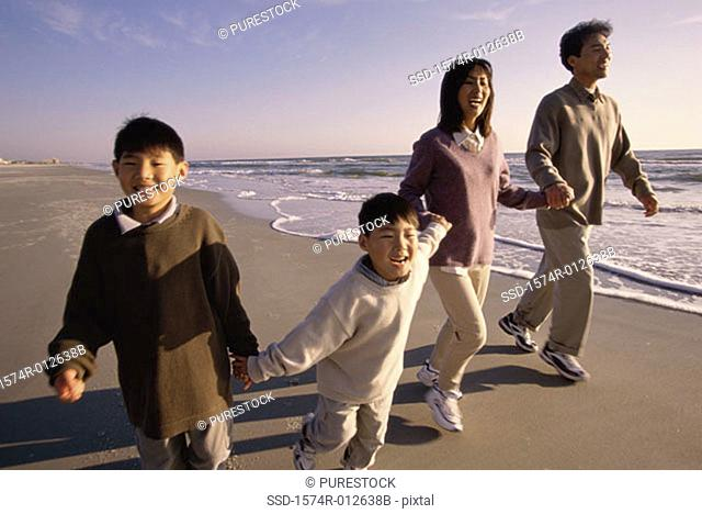 Parents with their two sons walking on the beach