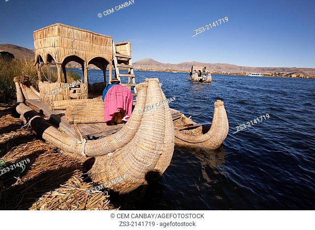 Aymara indigenous woman on a reed boat at the Uros Islands, Lake Titicaca, Puno Province, Peru, South America