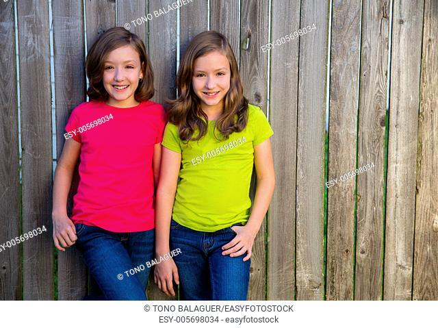 Twin sister girls with different hairstyle posing on wood backyard fence
