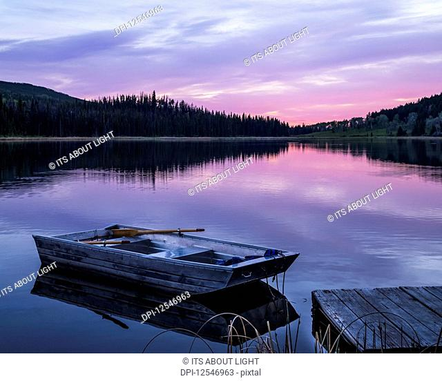 A wooden rowboat sits beside a dock on a tranquil lake reflecting the pink of a sunset, Lac Le Jeune Provincial Park; Kamloops, British Columbia, Canada