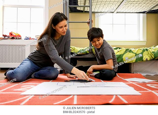 Mother and son sitting on floor of bedroom drawing on placard