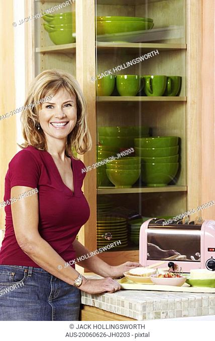 Portrait of a mature woman standing in the kitchen and smiling