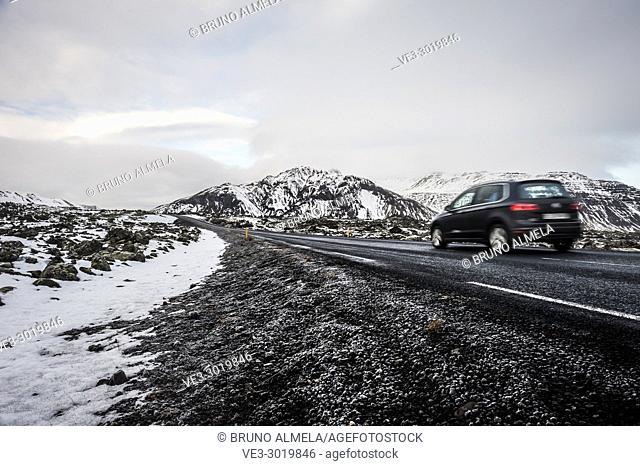 Car along route 54 crossing a lava field in Snæfellsnes peninsula (region of Vesturland, Iceland)