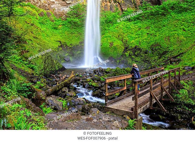 USA, Oregon, Multnomah County, Columbia River Gorge, Elowah Falls, Female tourist standing on bridge