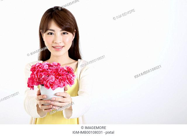 Young woman holding carnations and smiling at the camera