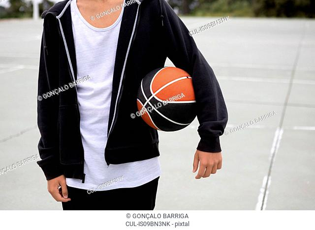 Male teenage basketball player on basketball court with ball under his arm, mid section
