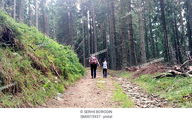 Mother and son climb the mountain road up hill holding hand Woman with backpack and child walking in forest nature