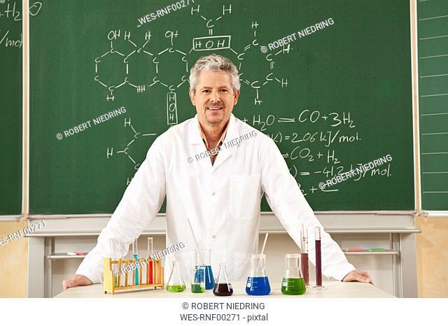 Germany, Emmering, Senior man standing in chemistry lab, smiling, portrait