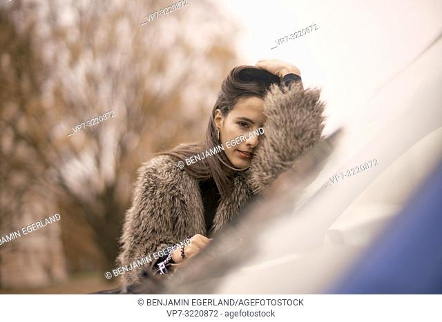 portrait of woman leaning on car window in city, pensive mood, Munich, Germany