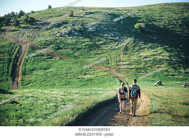 Caucasian couple walking on path toward hill