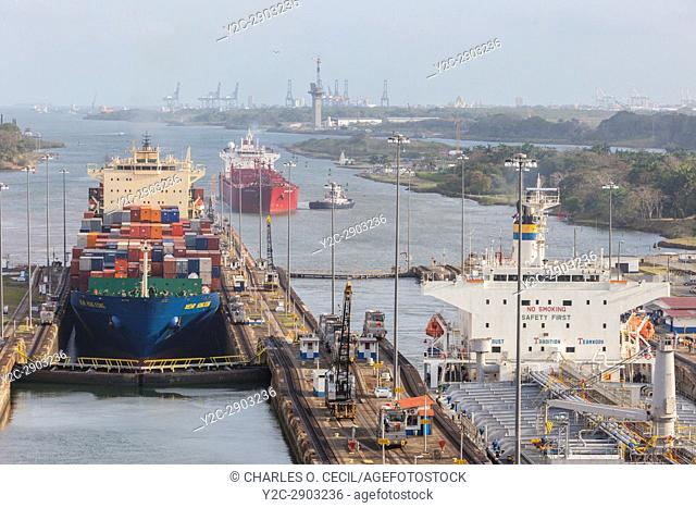 Panama Canal, Panama. Two Ships Entering First Lock Heading South, Caribbean in far rear. Third Ship Awaits its Turn. Colon Port Cranes in far Background