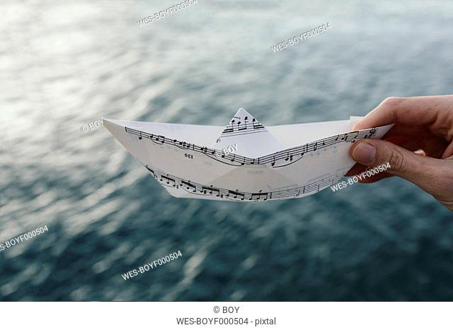 Hand at the water holding paper boat made of music sheet