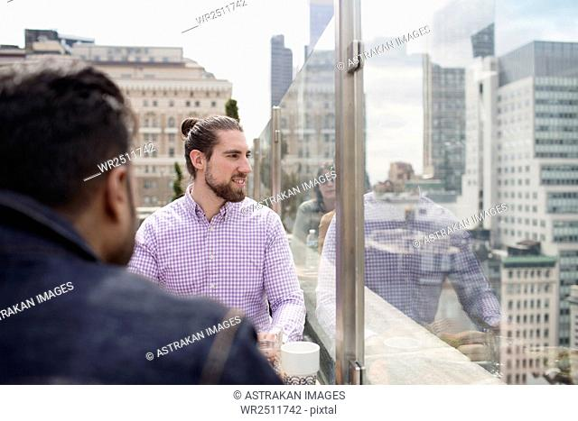 Men sitting at rooftop restaurant looking through glass